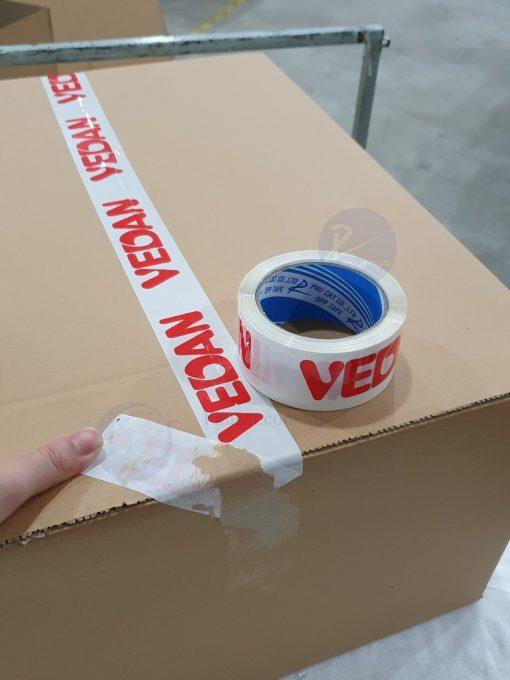 1 băng dính in logo đỏ nền trắng sứ khi dán trên thùng carton (4)