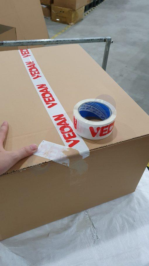 băng dính in logo đỏ nền trắng sứ khi dán trên thùng carton (1)